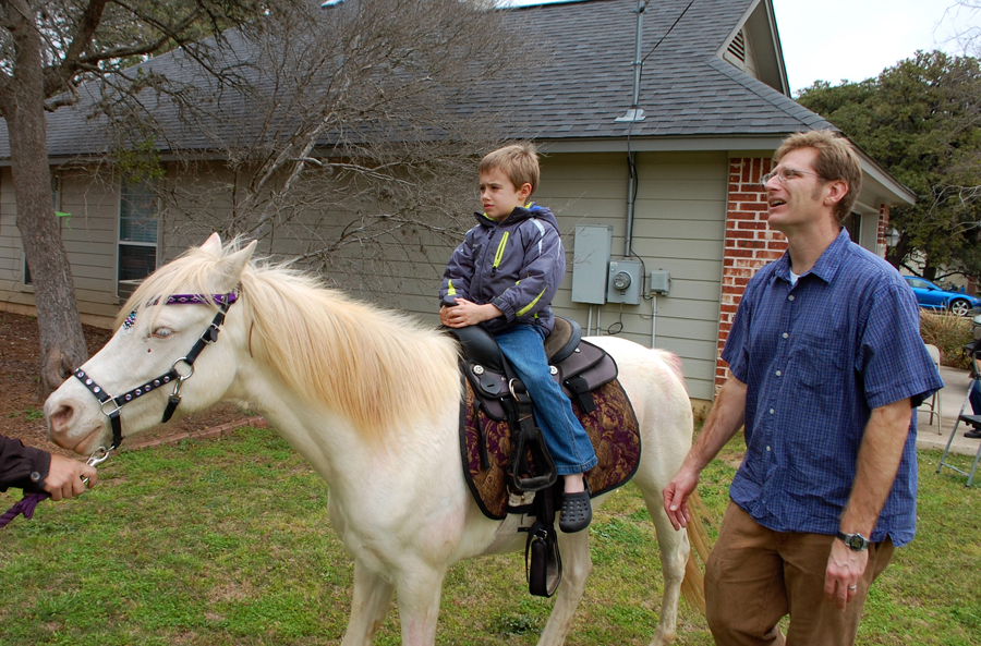 This boy was refusing to ride the pony but finally got on.